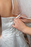 Female hands  corset bride. Female hands tightening a corset to the bride Stock Photo