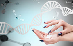 Female hands with cream over dna and molecules. Female hands with cosmetis cream over dna and molecules background Royalty Free Stock Photography