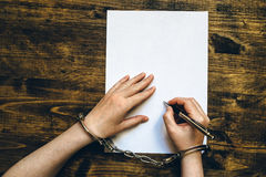 Female hands cuffed signing confession, top view Stock Images