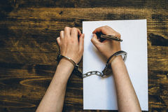 Female hands cuffed signing confession, top view Stock Photos