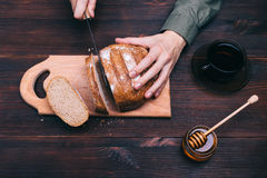 Female hands cut bread on the table Stock Image