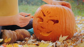 Female hands cut face on the pumpkin. Preparing for Halloween. Young woman carves a pumpkin. Sitting in the yard in the background of yellowing and orange trees stock footage