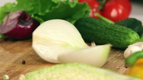 Female hands cut onion into two parts. Cooking - cutting onions in the kitchen stock footage