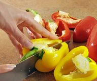 Female hands cut pepper Royalty Free Stock Photography