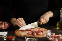 Female hands cut the raw meat into pieces on wooden board on dark table with seasoning and bottle of oil. stock images