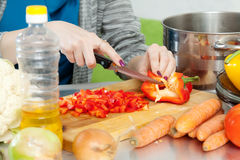 Female hands cuts pepper Stock Images