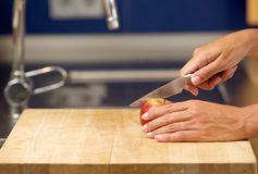 Female hands cutting apple on chopping board Royalty Free Stock Photography