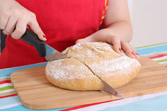Female hands cutting bread Stock Images