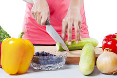 Female Hands Cutting Cucumber Stock Image