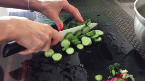 Female hands cutting cucumbers with ceramic knife stock video footage