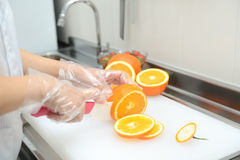 Female hands cutting fresh juicy orange Royalty Free Stock Photos