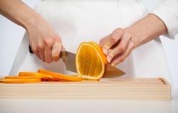 Female hands cutting fresh juicy orange Stock Image