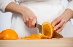 Female hands cutting fresh juicy orange Royalty Free Stock Image