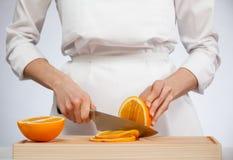 Female hands cutting fresh juicy orange Royalty Free Stock Photos