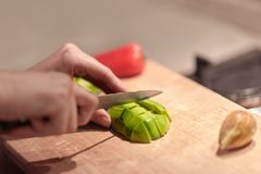 Female hands cutting fresh organic avocado with knife on wooden board in kitchen. Red bell pepper on background. royalty free stock photo