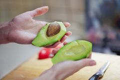 Female hands cutting fresh organic avocado to two peaces, pip inside. The knife and red bell pepper on wooden board in kitchen. royalty free stock image