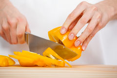 Female hands cutting fresh pepper Stock Photo