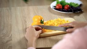 Female hands cutting fresh yellow pepper on chopping board in kitchen, cooking stock image