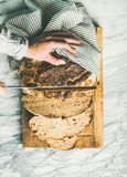Female hands cutting freshly baked sourdough bread, vertical composition Royalty Free Stock Photography