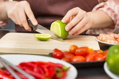 Female hands cutting green lime on wooden cutting board in her h stock image