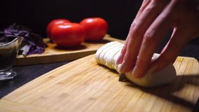 Female hands cutting mozzarella cheese on the wooden cutting board stock footage