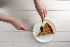 Female hands cutting a piece of pie on a white plate. Top view. Female hands cutting a tasty piece of pie on a white plate. Top view Stock Photos