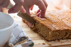 Female hands cutting and preparing cake crust Stock Image