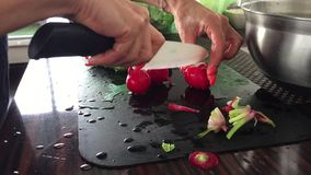 Female hands cutting radishes with ceramic knife stock video