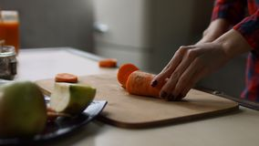 Female hands cutting raw carrot on chopping board stock footage
