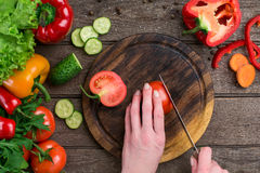 Female hands cutting tomato at table, top view. On the table vegetables and a wooden board Royalty Free Stock Photography