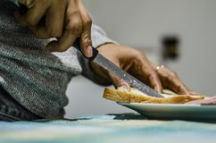 Female hands cutting wheaten bread on the wooden board stock photo