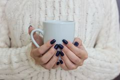 Female hands with dark blue nail design holding white cup. Royalty Free Stock Photo
