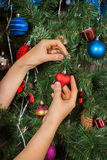 Female hands decorating christmas tree Stock Photos