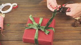 Female hands decorating gift red boxes for Christmas Holiday. Hands close up. stock video