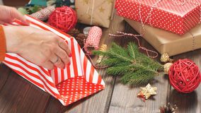 Female hands decorating gift red boxes for Christmas Holiday. Present packaging ideas.  stock video footage