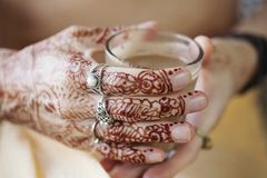Female hands decoratively colored by henna. With cup of masala tea Royalty Free Stock Images