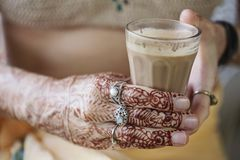 Female hands decoratively colored by henna. With cup of masala tea Stock Photos