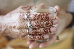 Female hands decoratively colored by henna. With cup of masala tea Stock Photography