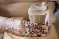 Female hands decoratively colored by henna. With cup of masala tea Royalty Free Stock Photo