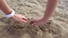 Female hands dig in sand and find gold bitcoin. Buried on the beach. Gold coin as a symbol of cryptocurrency stock video