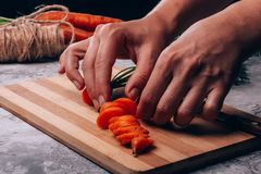 Female hands dilute slices of fresh carrots. Carrots sliced with slices of female hands are placed on a cutting board in the kitchen stock photos