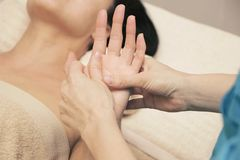 Massage therapist doing a therapeutic hand massage for a woman royalty free stock photo