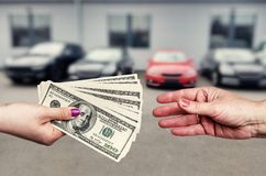 Female hands with dollar banknotes on background of cars row royalty free stock photos