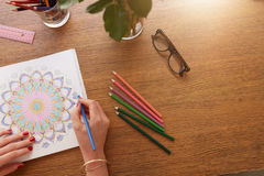 Female hands drawing in adult colouring book. Close up image of female hands drawing in adult colouring book on a table at home Royalty Free Stock Photos