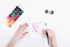 Female hands drawing with watercolors pink heart. Top view royalty free stock image