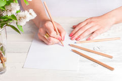 Female hands drawing on white wood Stock Photos