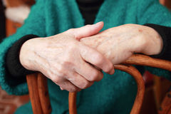 Female hands. Hands of an elderly woman lying on a chair Stock Photos