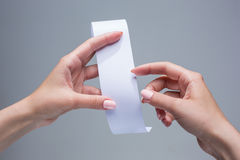 The female hands with  empty transaction paper or paper check. On gray background Royalty Free Stock Images