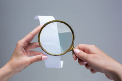 The female hands with  empty transaction paper or paper check and magnifier. The female hands with  empty transaction paper or paper check on gray background and Stock Photography