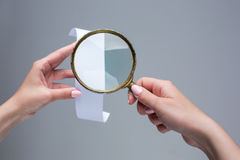 The female hands with  empty transaction paper or paper check and magnifier. The female hands with  empty transaction paper or paper check on gray background and Royalty Free Stock Images